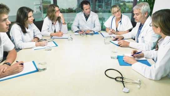 Clinicians reviewing updated cancer report.