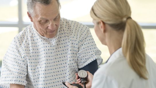 Elderly patient taking blood pressure