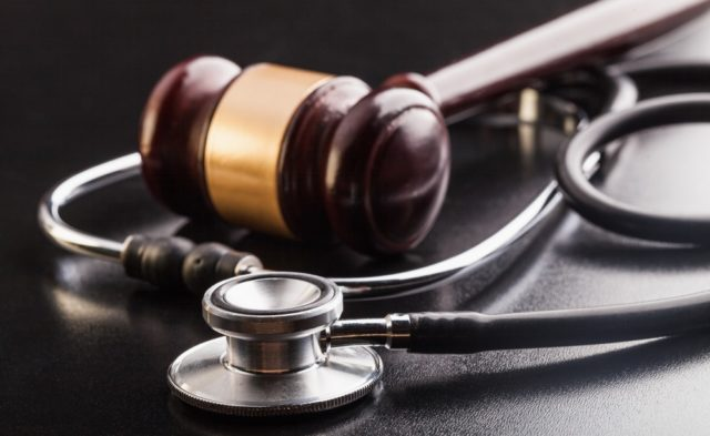 Image of a gavel entwined with a stethoscope