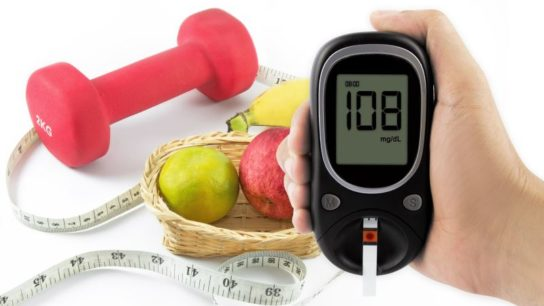 A glucometer with fruit and a tape measure in the background.