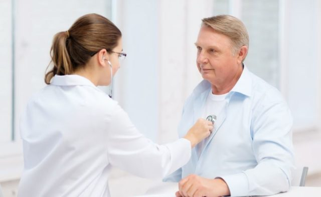 A physician listening to a man's heartbeat