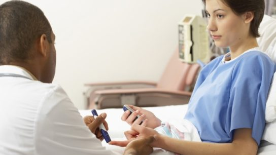 A doctor checks a patient's glucose levels in the hospital.