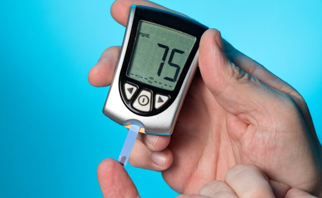 man checking blood sugar