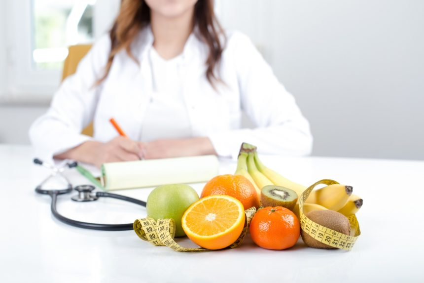 nutritionist with fruits on her desk