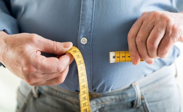 overweight man with measuring tape around his stomach
