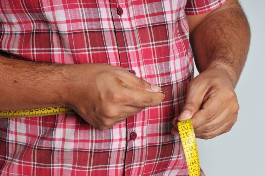 An overweight man measuring his waist
