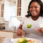Overweight woman eating healthy meal