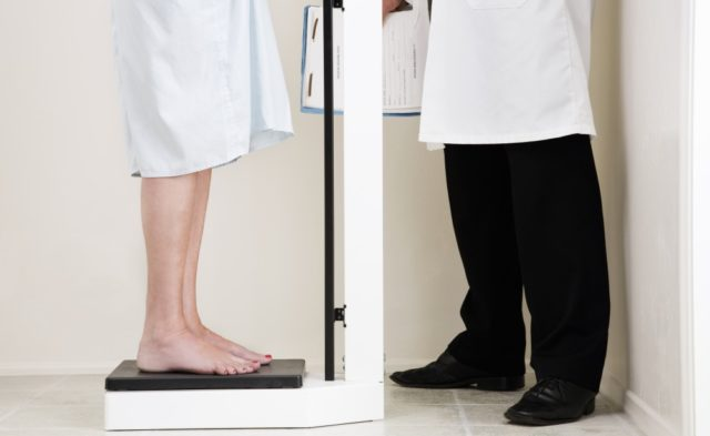 Woman standing on a scale in physician's office