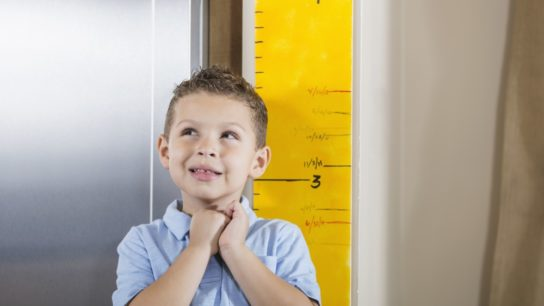 Young boy having height measured.