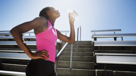 A female athlete drinks water after exercising.