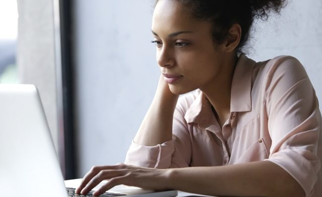 Young woman looking at laptop.