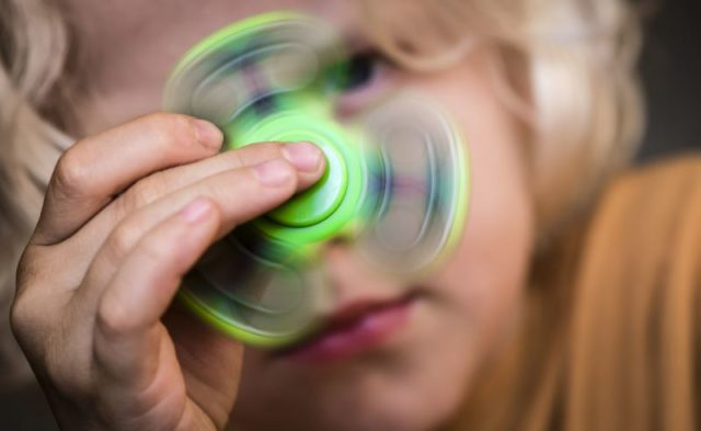 A child with ADHD playing with a fidget spinner.