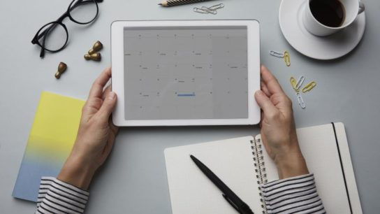 A woman viewing a calendar on a tablet