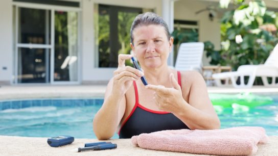 A woman testing her blood glucose levels before or after exercising in a swimming pool.