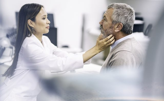 Female doctor checking male patient throat