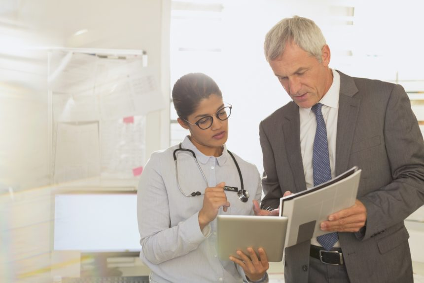 Doctors reviewing data on digital tablet.
