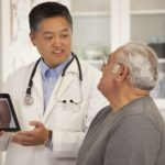 Doctor with tablet talking to older man