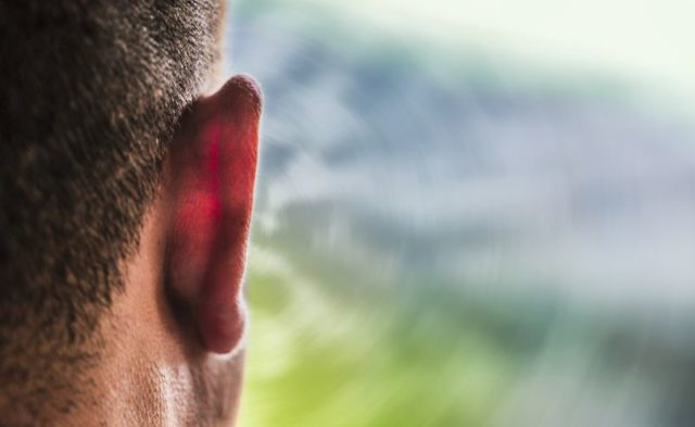 A close-up of a man's ear with conceptual sound waves