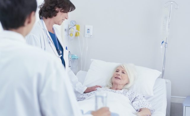 Two clinicians speaking with a patient in a hospital room