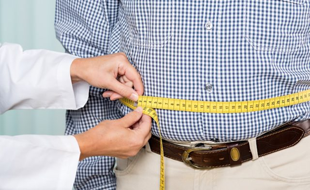 overweight man being measured