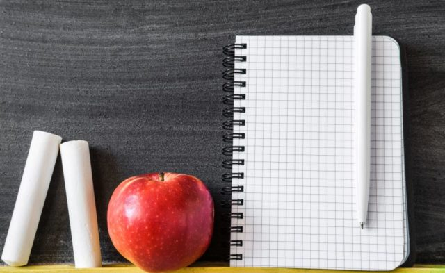 A chalkboard with a notebook and an apple on the ledge