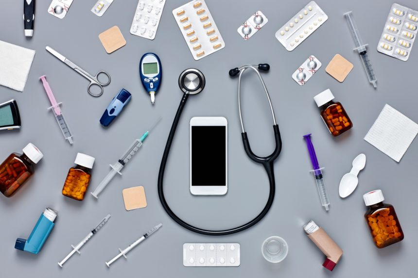 Flat lay of smart phone surrounded with various medical equipment