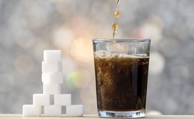 A glass of soda next to sugar cubes