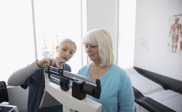 A postmenopausal woman being weighed at a physician's office