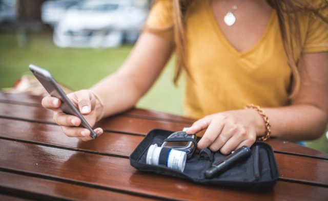 woman with cell phone and diabetes kit
