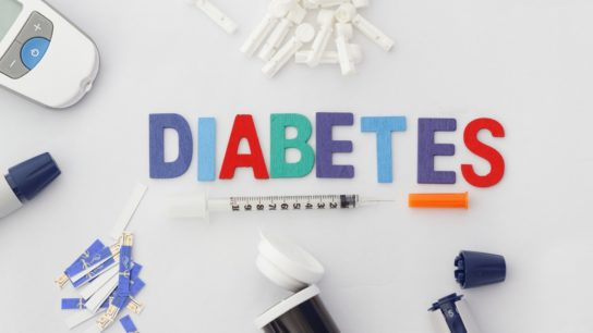Word diabetes surrounded by supplies for diabetes management