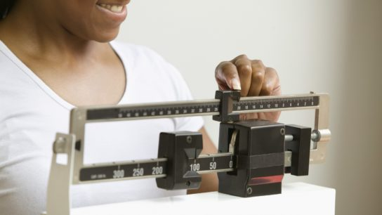woman measuring her weight on scale