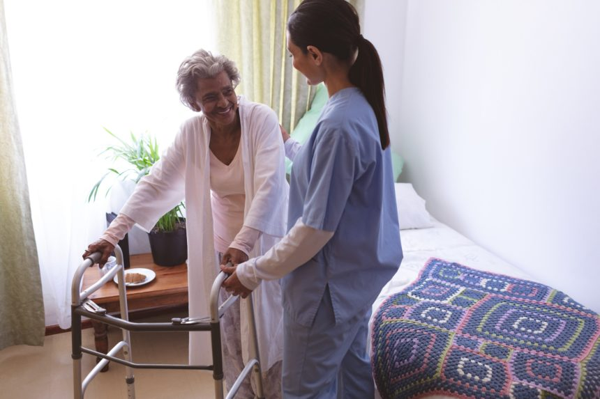 nurse helping senior female patient to stand with walker