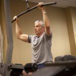 man exercising on lat pull down