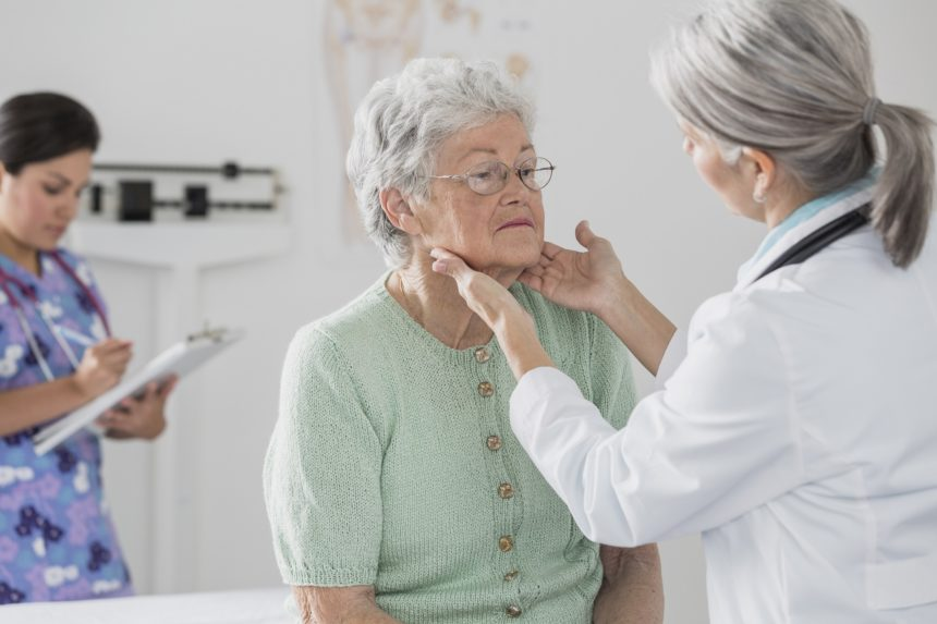 older woman getting thyroid exam