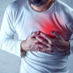 man clenching chest in pain