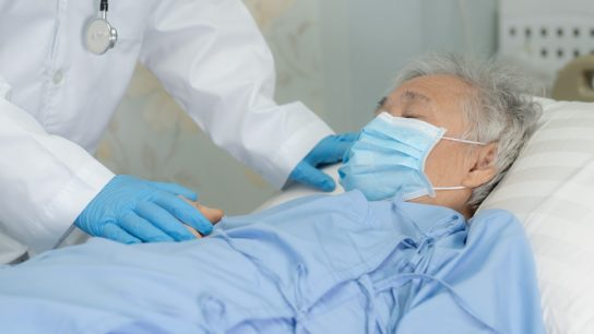 Doctor Examining Masked Patient In Hospital
