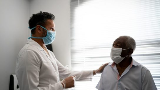 doctor with older Black patient wearing mask