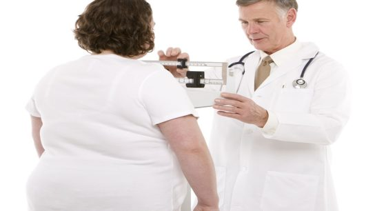 Overweight women being weighed by doctor