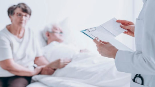 doctor reviewing patient chart at hospital bedside